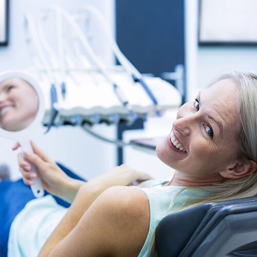 Woman sitting on dental chair smiling while holding a mirror