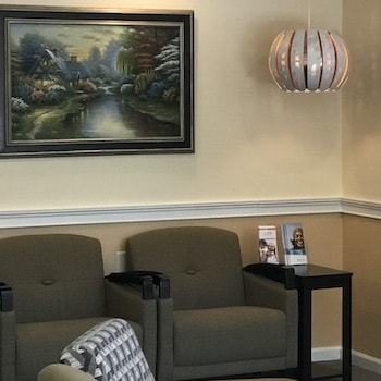 Our waiting room with couches, a painting, and comfortable feel