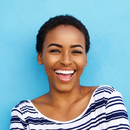 Dental Services Gastonia, NC - Short-haired female laughing in front of a bright blue background