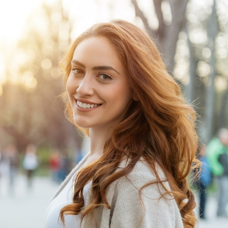 Red hair female looking over her shoulder and smiling with her new veneers