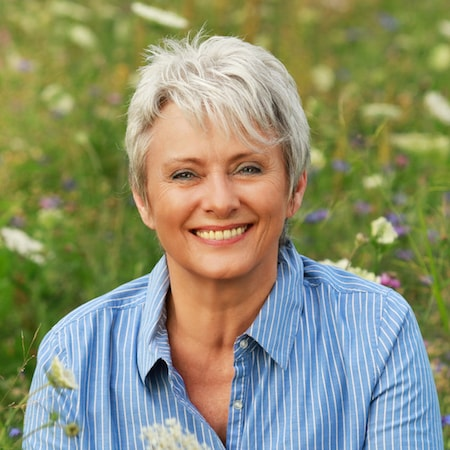 Dental Services Gastonia, NC - Older female with short grey hair, wearing a jean shirt, and smiling in a field of yellow flowers