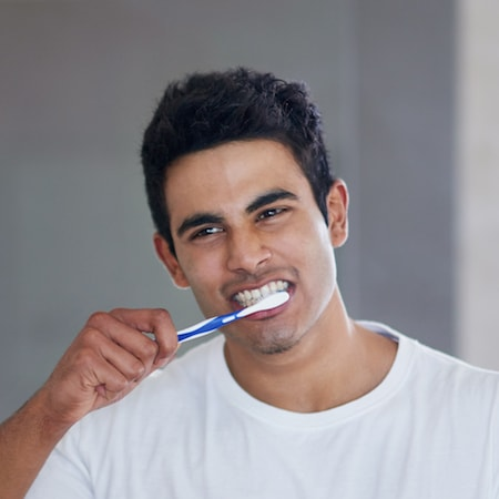 Dental Services Gastonia, NC - Dark-haired man wearing a white t-shirt while he brushes his teeth