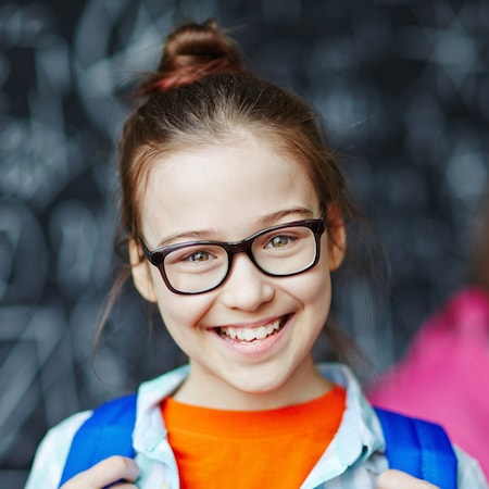 Dental Services Gastonia, NC - Young girl wearing glasses and wearing a backpack while see smiles with sealants