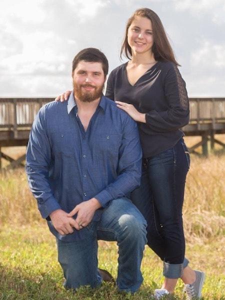 Enhanced Smiles Team Member - Tiffany standing next to her partner as he kneels on one knee in a field